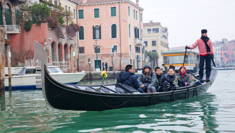 Gondolier sailing in Venice Grand channel with chinese tourists