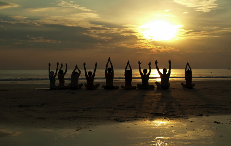 Group of people practicing yoga at sunset by the ocean