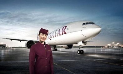 Qatar Airways Flight Attendant standing in from of air plane