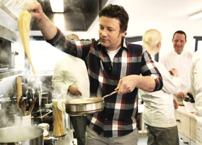 Jamie Oliver in a kitchen cooking pasta