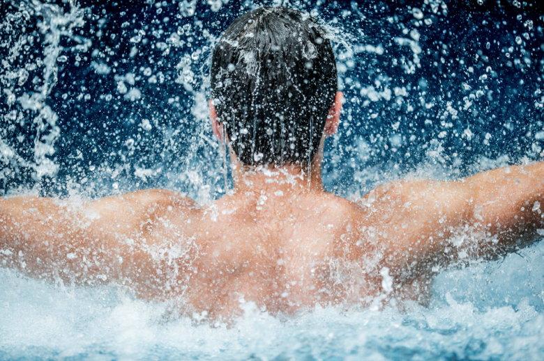 Young man enjoyimg a waterfal massage in a spa resort pool