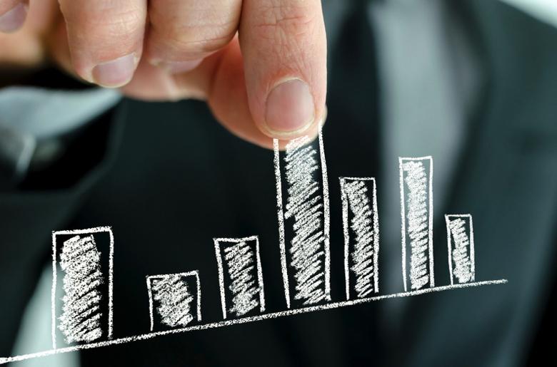 Businessman pulling graph column upwards