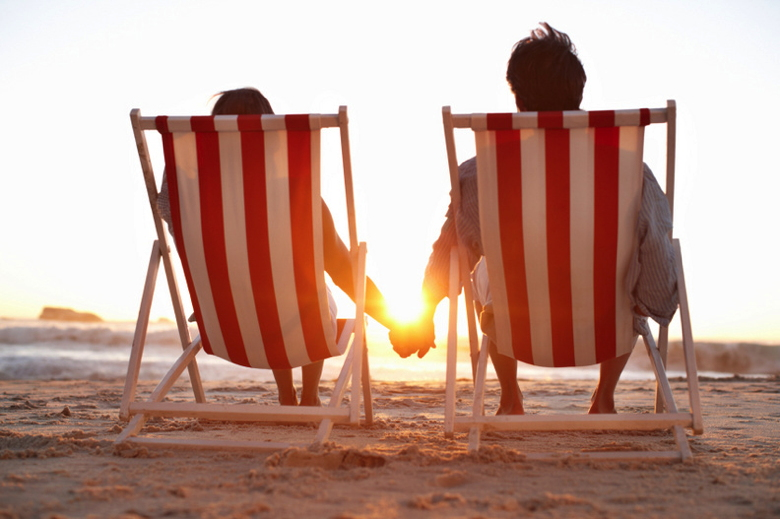 A couple sitting in chairs on the beach