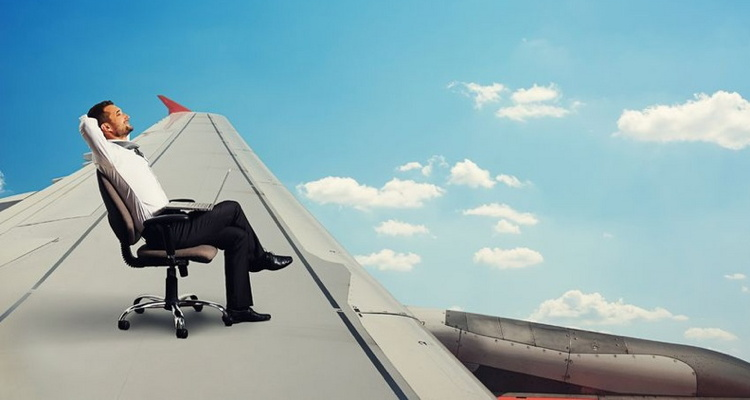 smiley businessman flying and resting on the wing of an airplane