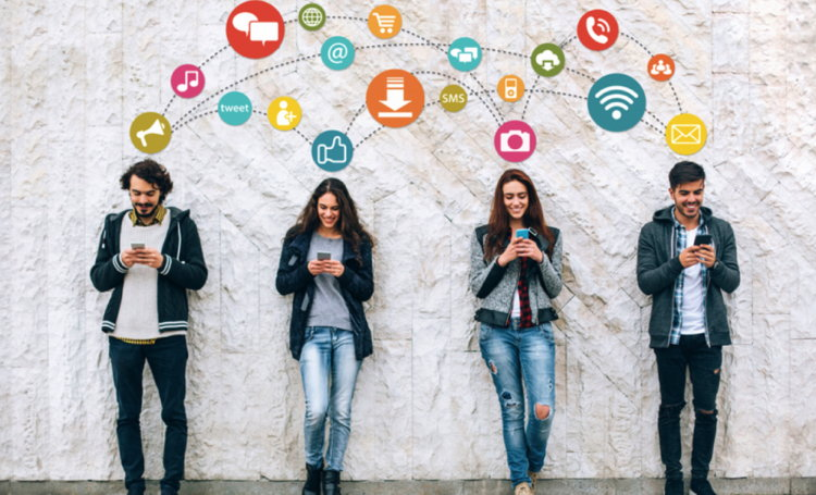 Four young people leaning against a wall and using smartphones