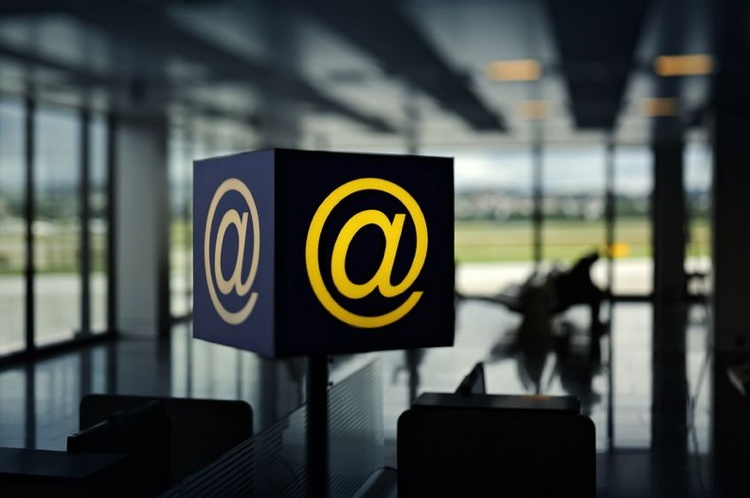 Internet sign inside Airport with businessmen sitting on waiting benches for the flight