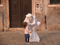 Young girl interacting with mime in Venice
