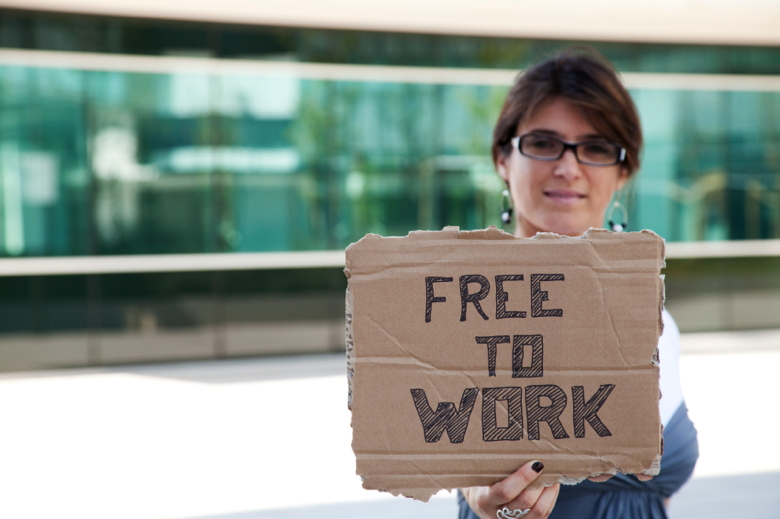 Woman Holding a cardboard sign saying free to work