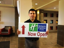 Holiday Inn Express hotel employee holding sign that says 'Now Open'