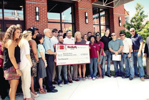 This photo released by Mugshots Grill & Bar shows the presentation of a $10,000 check to the Prescott House Child Advocacy Center as a result of a fundraising event at the restaurant.