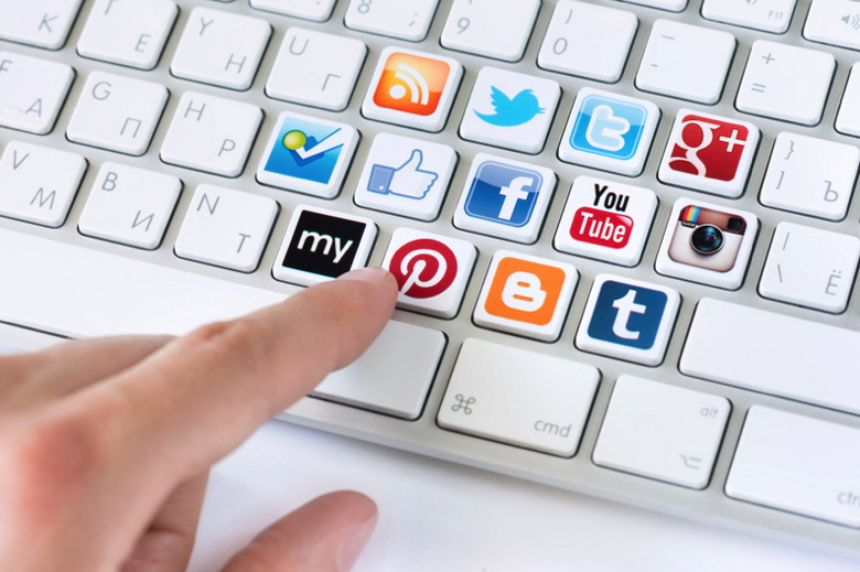 Hand pointing on keyboard with social media logotype collection of well-known social network brand's placed on keyboard buttons.