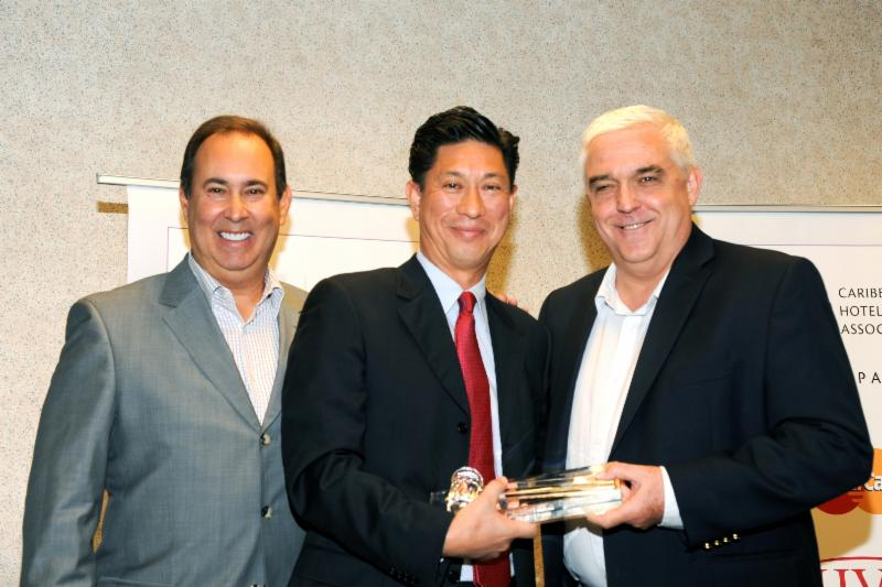 Photo caption: The Caribbean Hotel and Tourism Association (CHTA) inaugurated Emil Lee (pictured center), general manager of Princess Heights Hotel, St. Maarten, as the new president at its Annual General Meeting (AGM) on July 1, 2014. Richard J. Doumeng, (pictured right), immediate past president of CHTA and managing director of Bolongo Bay Beach Resort, St. Thomas, USVI, ceremoniously turns over the gavel to Lee along with Jeffrey S. Vasser, CHA, director general and CEO of CHTA.