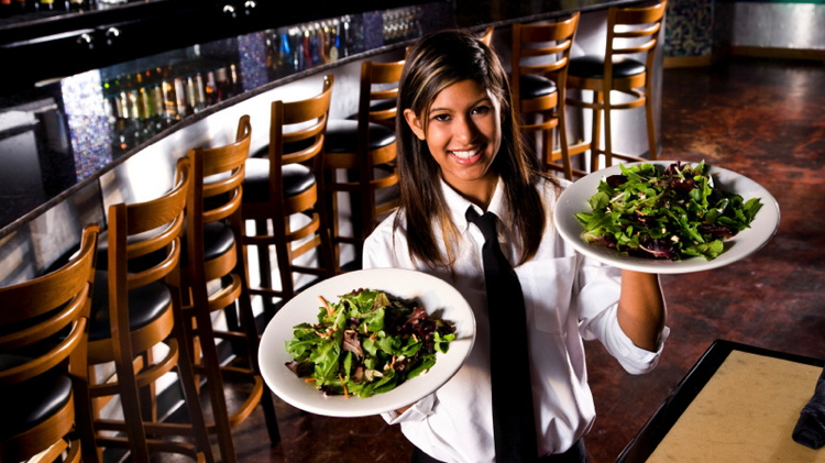 Smiling waitress serving salads