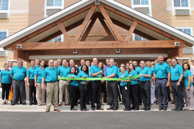 Local officials, WoodSpring Suites associates, and hotel guests gather for the celebratory ribbon-cutting marking the grand opening of WoodSpring Suite's first namesake hotel.