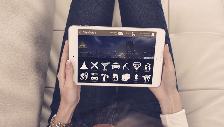 A woman holding an iPad showing the ButlerPad application
