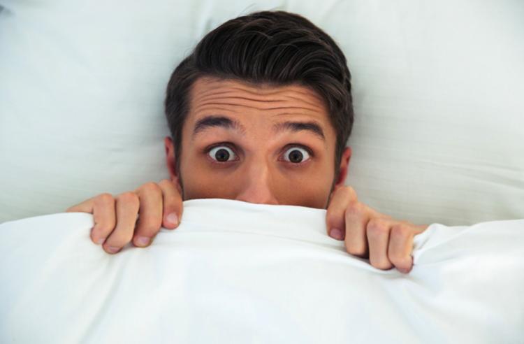 A scared man under a sheet