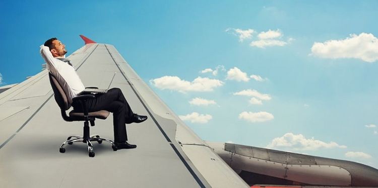 businessman flying and resting on the wing of an airplane