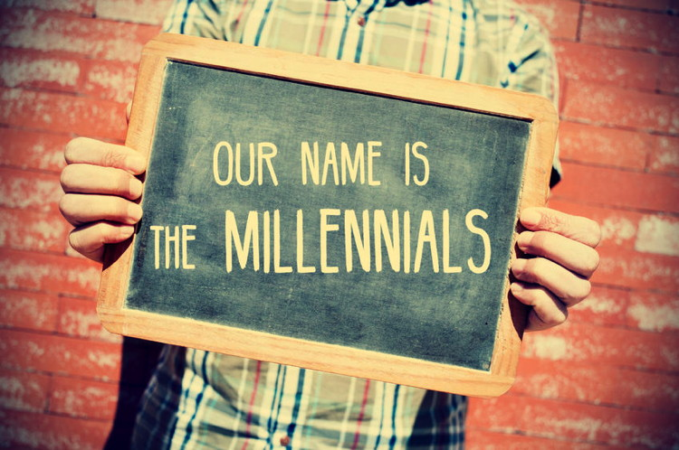 closeup of a young man holding a chalkboard with text our name is the millennials in front of a brick wall