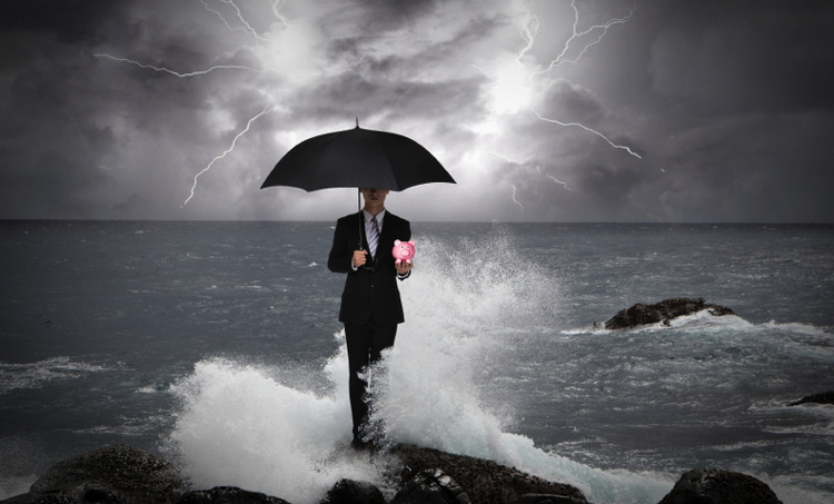 A man holding an umbrella in front of the ocean with dark skies