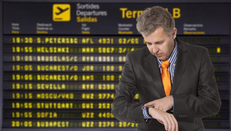 Flight delay. Businessman looking at his watch.