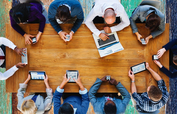 A group of people at a conference table using various mobile devices