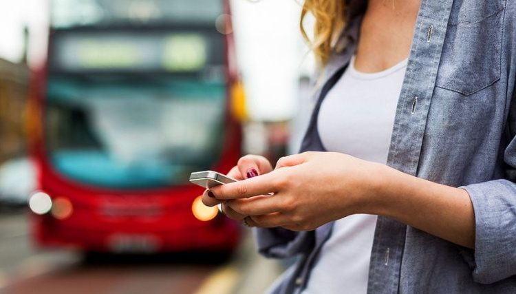A woman holding a cell phone in fron of a bus