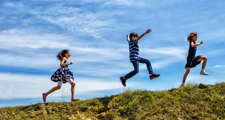 Children skipping and jumping up a hill
