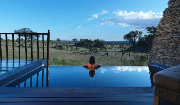 A woman in an infinity pool overlooking the Serengeti