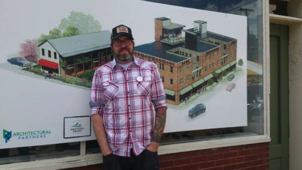 Renowned Chef Travis Milton in front of concept drawing for the Western Front Hotel, St. Paul, Virginia
