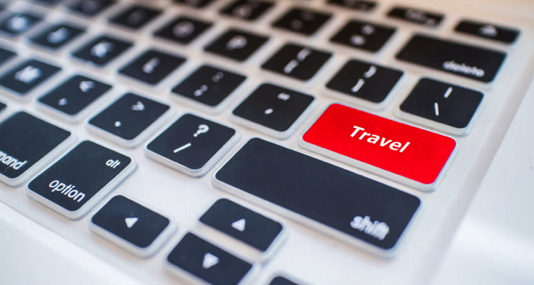 Close-up view on conceptual keyboard with the key 'travel' in red