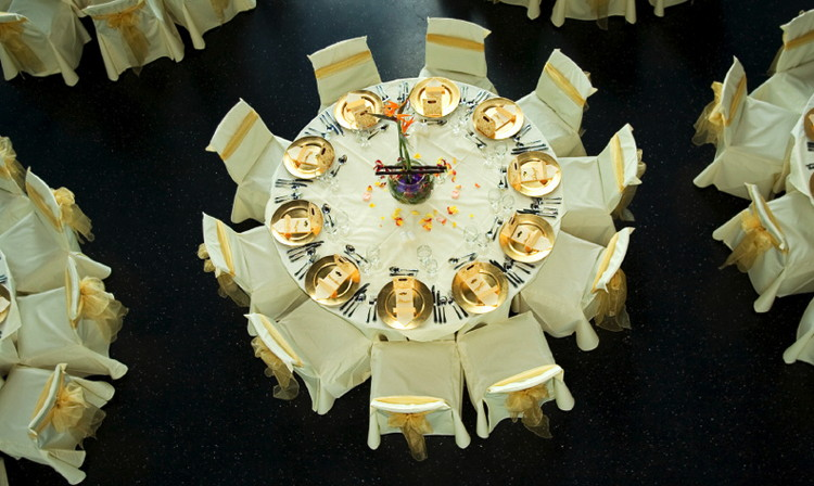 Wedding Reception Setting taken from above with Gold Plates and exotic Flower Table Display with sprinkled fresh rose Petals