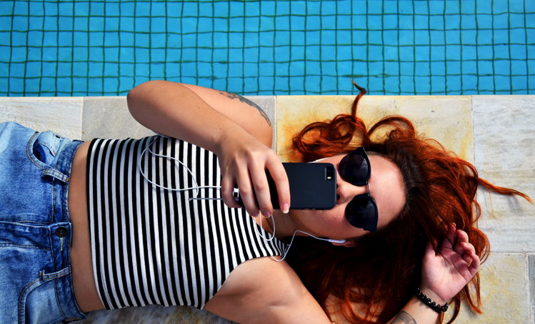 A woman by a pool using a mobile phone