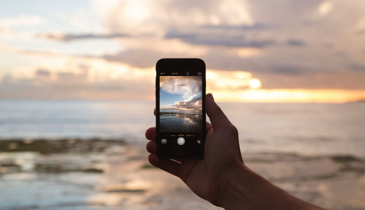A person holding a mobile phone and taking a photo at the beach - Unsplash