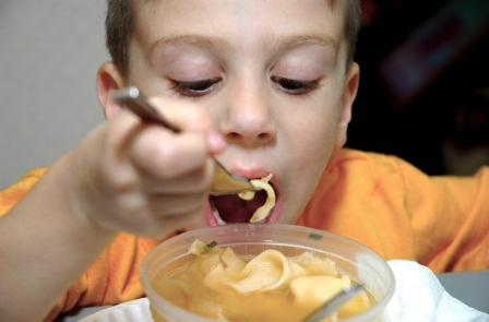 A kid eating pasta