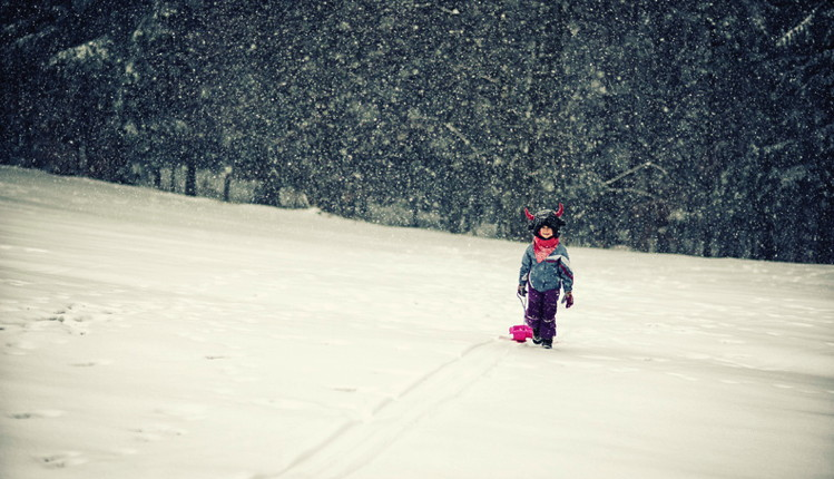 Little girl pulling a sled in snow