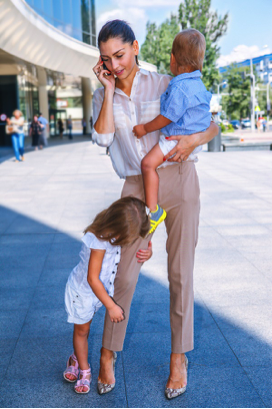 A woman with two children talking on a cell phone