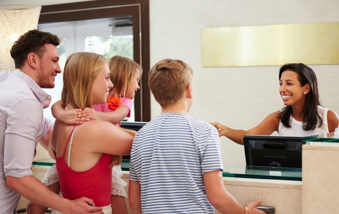 A family checking into a hotel - Source AHLA