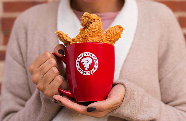 A woman holding Popeyes cup