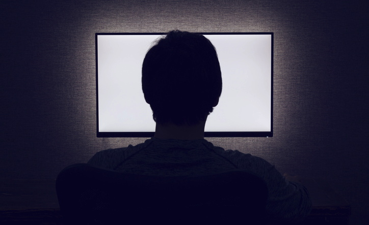 Silhouette of a man in front of a screen