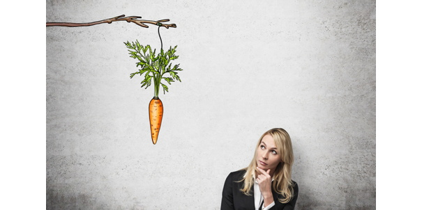 A woman looking up at a branch with carrot dangling