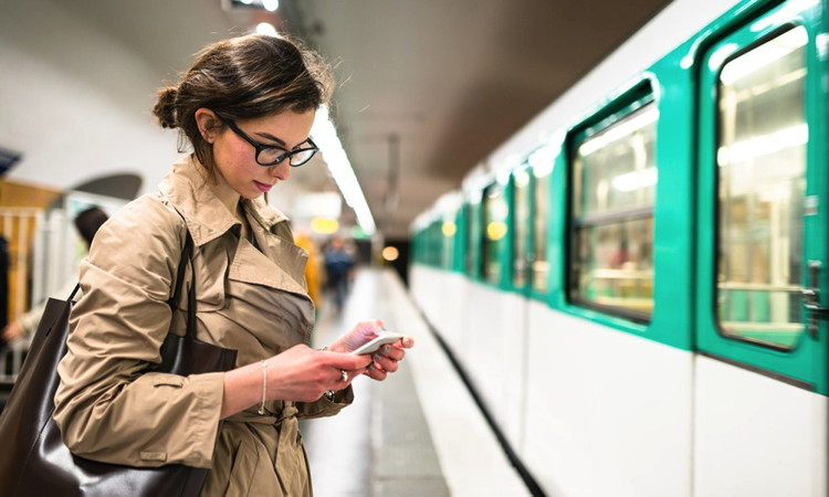 A woman using a smartphone on a subway platform