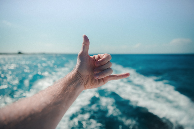 A man with a 'thumbs up' on a boat