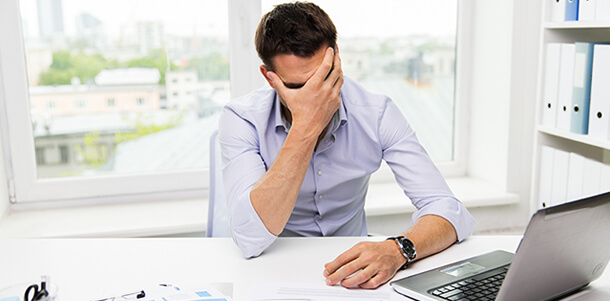 A man that appears to be stressed in front of a computer