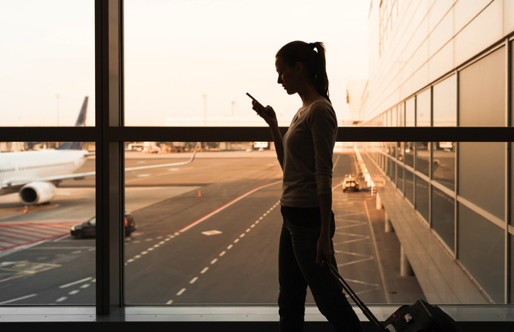 A woman in an airport terminal looking at her smart phone