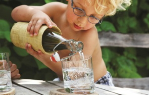 A child puring a glass of water