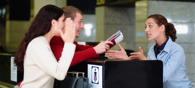 Guests talking to an agent at a hotel reception desk
