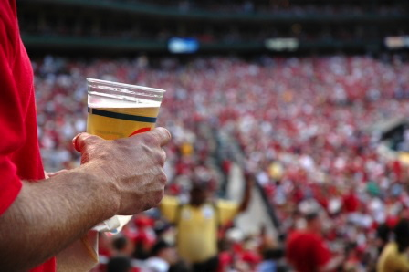 A man holding a beer in a stadium