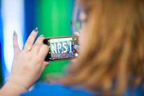 A woman taking a cellphone photo at NPSAI