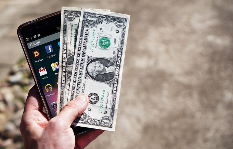 A mobile phone and dollar bills