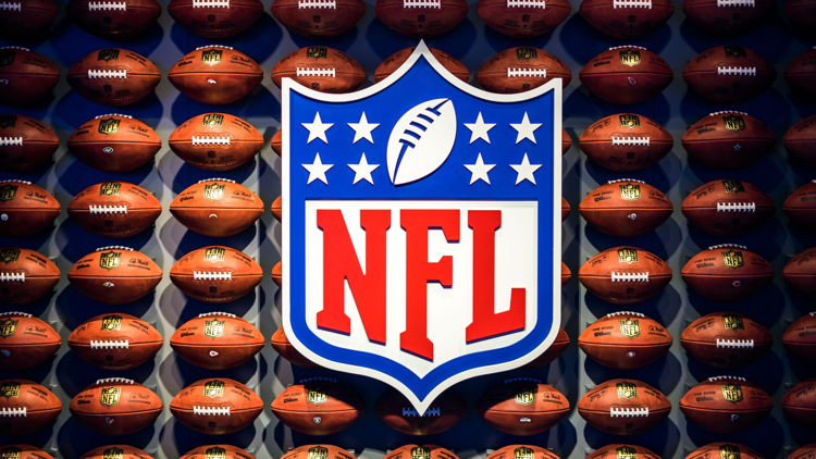 NFL logo with footballs in the background - Photo by Adrian Curiel on Unsplash